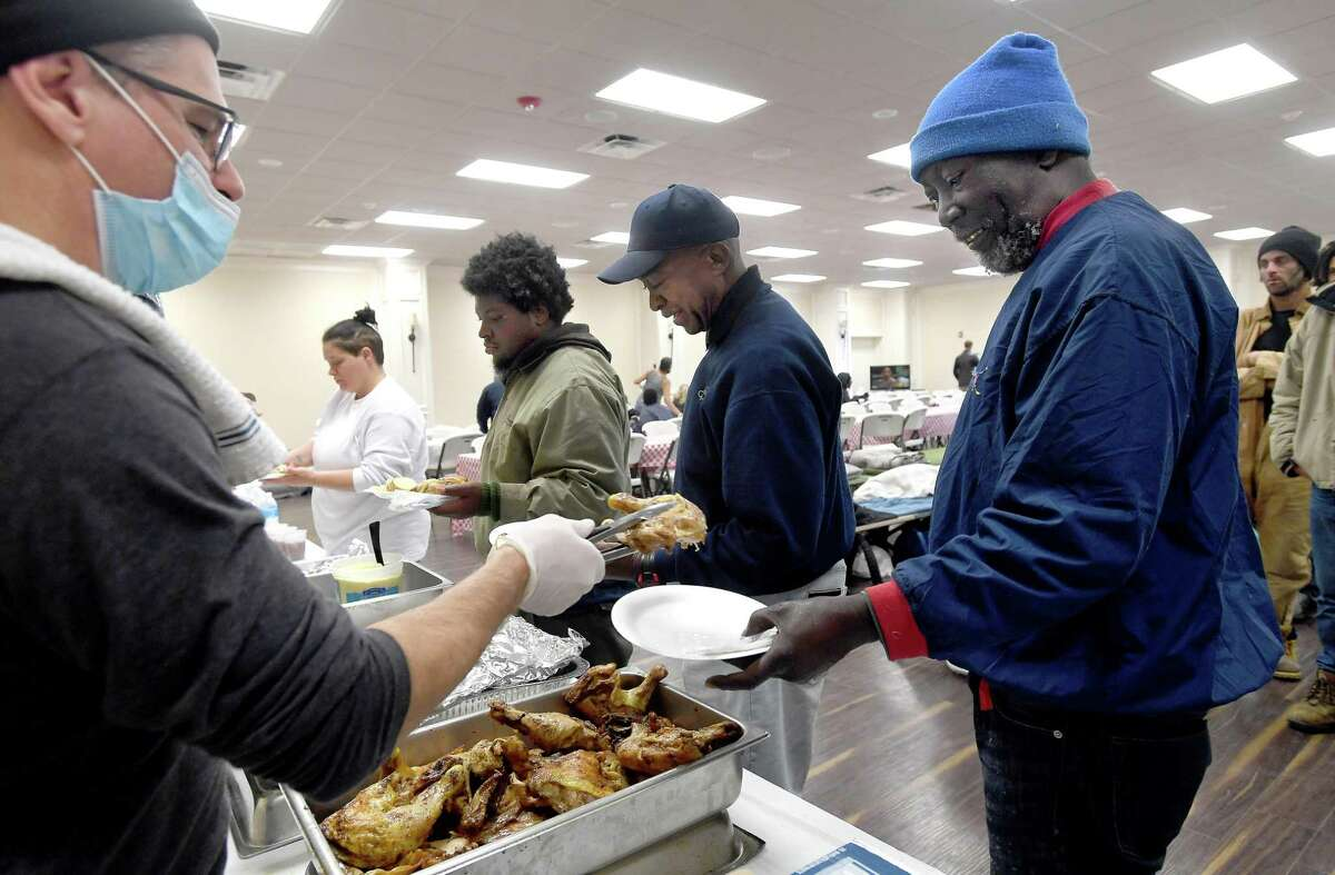 Billy Campbell serves chicken to Donald Bias as lunch is served at Victory Temple in Beaumont, which opened to those in need of shelter from the storm Saturday and will remain open through Friday morning. Bias has been living outside at the downtown bus station for three months sinnce completing his parole and having to leave the halfway house at which hhe had been staying. He suffers from multiple health conditions, has been running out of his medication, and receives only $265.00 a month from his railroad pension.