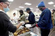"Billy Campbell serves chicken to Donald Bias as lunch is served at Victory Temple in Beaumont, which opened to those in need of shelter from the storm Saturday and will remain open through Friday morning. Bias has been living outside at the downtown bus station for three months sinnce completing his parole and having to leave the halfway house at which hhe had been staying. He suffers from multiple health conditions, has been running out of his medication, and receives only $265.00 a month from his railroad pension. ""That isn't enough to pay for anything"" to find housing, he says. Bias is still trying to get social security, and volunteers at the shelter are working to fill his prescriptions. When a volunteer came to the bus station Sunday, he was the only one who accepted the ride to the shelter. He says the dope some on the streets are smoking affects their judgement. ""They aren't able to make the right decisions,"" he says, but as temperatures continued to worsen, he has since seen some arrive for shelter. ""I'm staying put,"" he says, ""I'm gonna stay here through Friday"" before likely returning to the bus stop. Photo made Tuesday, February 16, 2021 Kim Brent/The Enterprise"