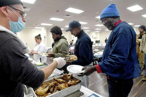 """Billy Campbell serves chicken to Donald Bias as lunch is served at Victory Temple in Beaumont, which opened to those in need of shelter from the storm Saturday and will remain open through Friday morning. Bias has been living outside at the downtown bus station for three months sinnce completing his parole and having to leave the halfway house at which hhe had been staying. He suffers from multiple health conditions, has been running out of his medication, and receives only $265.00 a month from his railroad pension. """"That isn't enough to pay for anything"""" to find housing, he says. Bias is still trying to get social security, and volunteers at the shelter are working to fill his prescriptions. When a volunteer came to the bus station Sunday, he was the only one who accepted the ride to the shelter. He says the dope some on the streets are smoking affects their judgement. """"They aren't able to make the right decisions,"""" he says, but as temperatures continued to worsen, he has since seen some arrive for shelter. """"I'm staying put,"""" he says, """"I'm gonna stay here through Friday"""" before likely returning to the bus stop. Photo made Tuesday, February 16, 2021 Kim Brent/The Enterprise"""