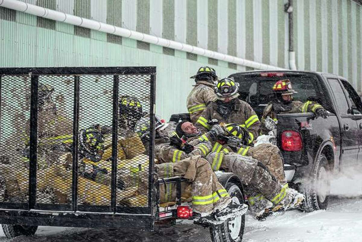 FILE - A group of firefighters take a well-deserved break after fighting a large fire at R. P. Lumber in Edwardsville. Fire crews were on the scene for more than 12 hours.