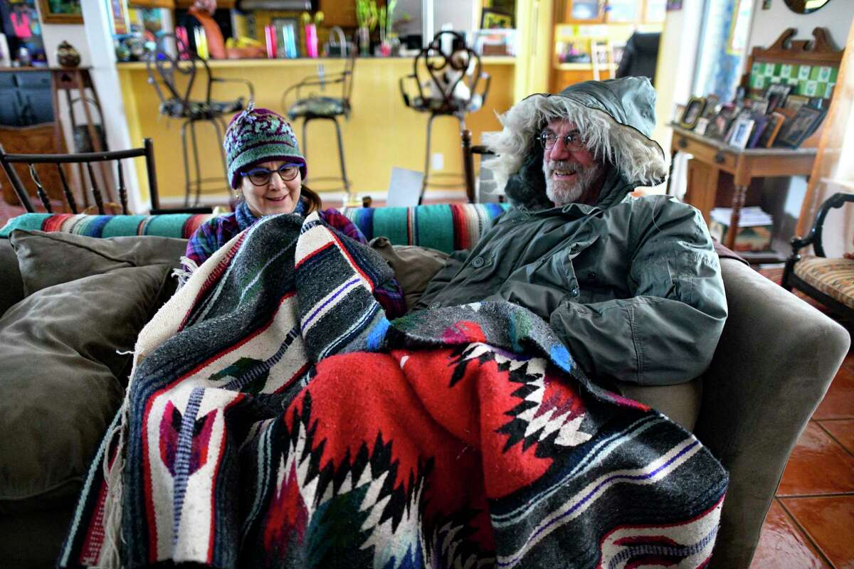 George and Alissa Baugh keep warm under blankets in their home on Tuesday, Feb. 16, 2021. They had no power as of Tuesday morning due to the effects of the cold and snow. They regained it in the afternoon. George Baugh said that he had once thought of getting rid of his heavy coat, but is now glad that he didn't.