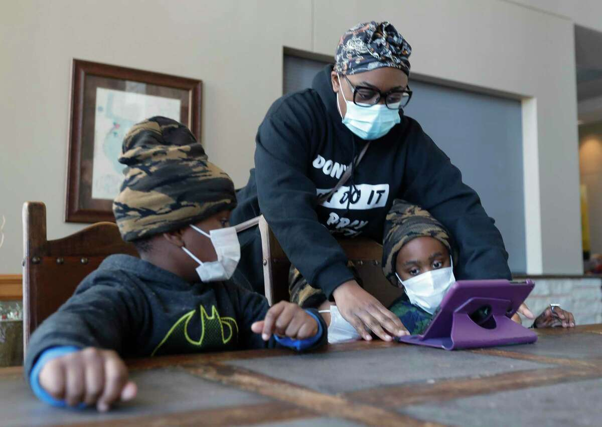 """Angelia Toliver helps set up an iPad for her sons, Zechariah and Mack, at a shelter setup at the Lone Star Convention & Expo Center, Tuesday, Feb. 16, 2021, in Conroe. The family came to the shelter after their home loss power yesterday. """"We're just came here to get warm for a while,"""" Angelia said. """"We're hoping we get power today, but if not we will probably come back to have somewhere warm to sleep."""