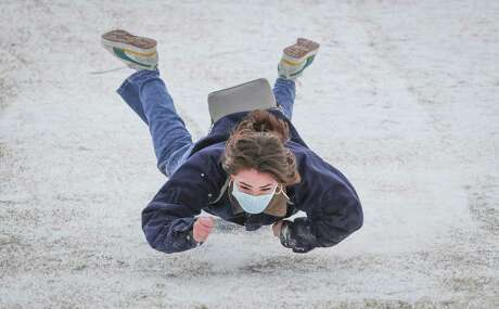 Rice University student Belen Szentes becomes airborne after her plastic bin lid stopped while she was sledding on the Miller Outdoor Theatre hill Monday, Feb. 15, 2021, in Houston.