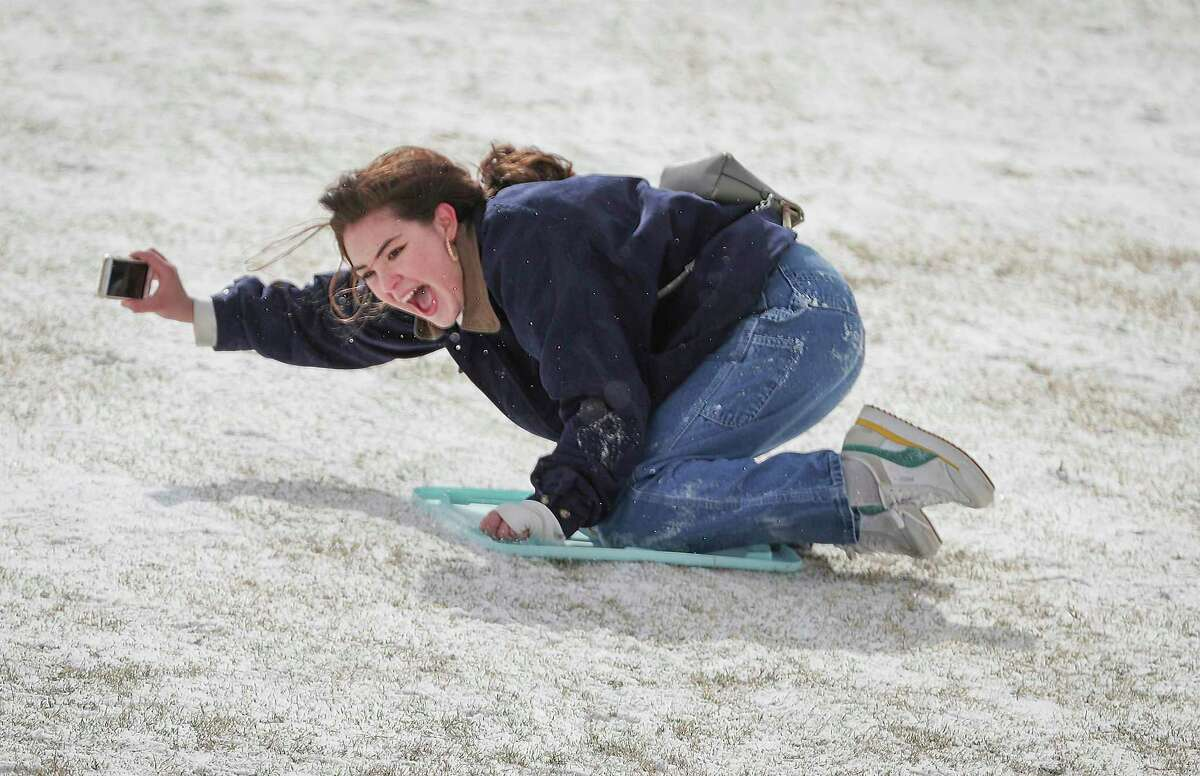 Rice University student Belen Szentes documents her sled ride on the Miller Outdoor Theatre hill Monday, Feb. 15, 2021, in Houston. (Steve Gonzales/Houston Chronicle via AP)