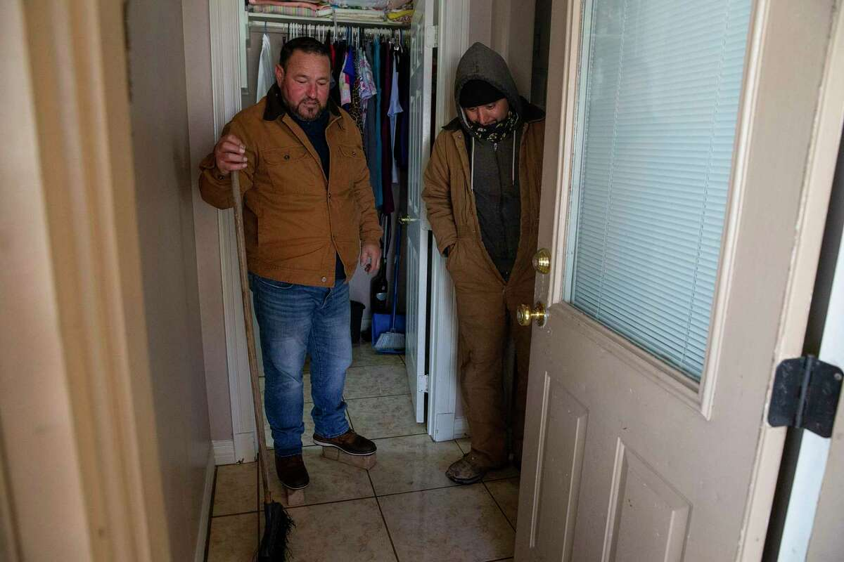 South Houston Councilmember Willie RÌos, right, looks at the water damage with Jacob Chapa in Chapa's mother-in-law's house Tuesday, Feb. 16, 2021, in South Houston. Sylvia Gomez lost power at her house and went to stay with her daughter in Pasadena last night, but came home to find her water pipes bursted and flooded her house.