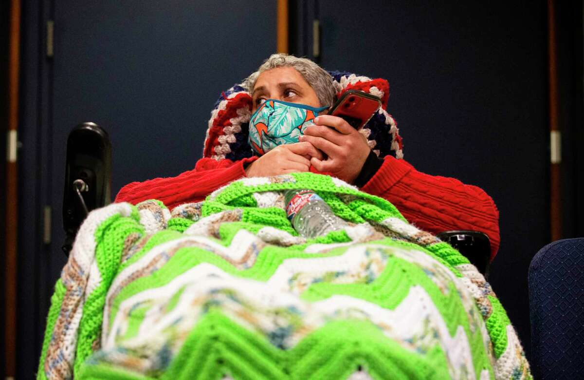 Maria Laboy talks to people on the phone while staying at Lakewood Church Tuesday, Feb. 16, 2021, in Houston. Laboy came to the warm center on Monday night due to lost of power at her place.