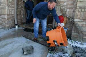 Jacob Chapa dumps water pumped out of his mother-in-law's house Tuesday, Feb. 16, 2021, in South Houston. Sylvia Gomez lost power at her house and went to stay with her daughter in Pasadena last night, but came home to find her water pipes bursted due to the cold weather and flooded her house. They had to rent a water suction pump to pump the water on the floor.