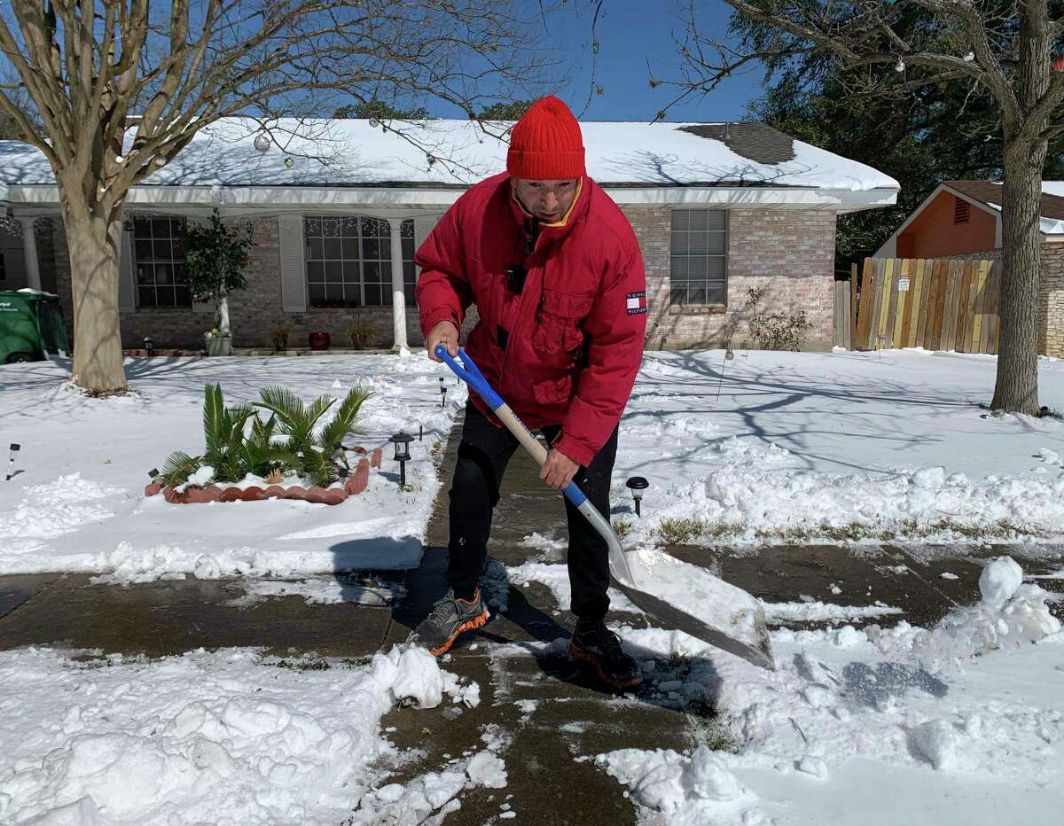 Saul Cortez shovels snow from the sidewalk in front of his home in the Harmony Hills neighborhood on Monday, Feb. 15, 2021, after inches of snow fell overnight. He said that he is from New Jersey, where the snow that fell in San Antonio would be considered a mild annoyance.