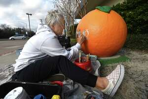 On a recent Thursday, local artist Lauren Leigh Stanley continued work on the Orange City Hall painting of the orange fixture that sits outside the site. Stanley has done roughly 25 of the city's orange decorations, many themed to the business at hand, and others reflecting the community at large, like the piece she is doing outside City Hall. She is already commissioned for ten more pieces and is booked through April for work. The Houston transplant says she is so grateful for the community and the opportunity it has given her to pursue her lifelong love of art. It started when she was in second grade, and a spark for art was born by an art teacher. Now, her children get to see their mother doing something she loves and celebrating a community she has embraced as it has embraced her. Photo taken Thursday, February 4, 2021 Kim Brent/The Enterprise