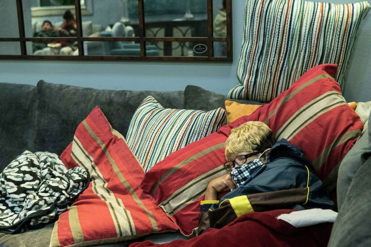 Debra Bracey, who lost power at her home Monday evening, rests on a couch at a warming shelter set up at Gallery Furniture Tuesday, Feb. 16, 2021 in Houston. As emperatures stayed below freezing Tuesday, and many in the neighborhood around the furniture store without power, Jim