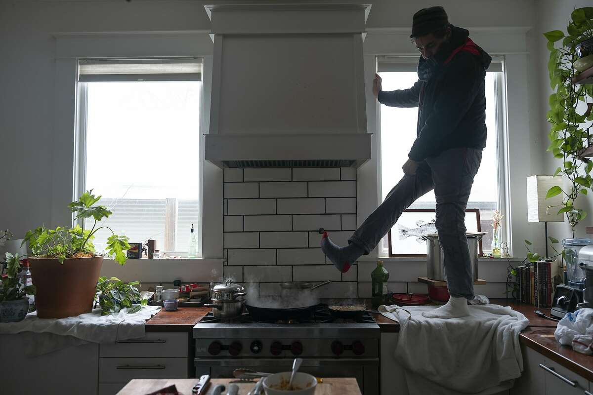 Jorge Sanhueza-Lyon stands on his kitchen counter to warm his feet over his gas stove Tuesday, Feb. 16, 2021, in Austin, Texas. Power was out for thousands of central Texas residents after temperatures dropped into the single digits when a snow storm hit the area on Sunday night. (AP Photo/Ashley Landis)