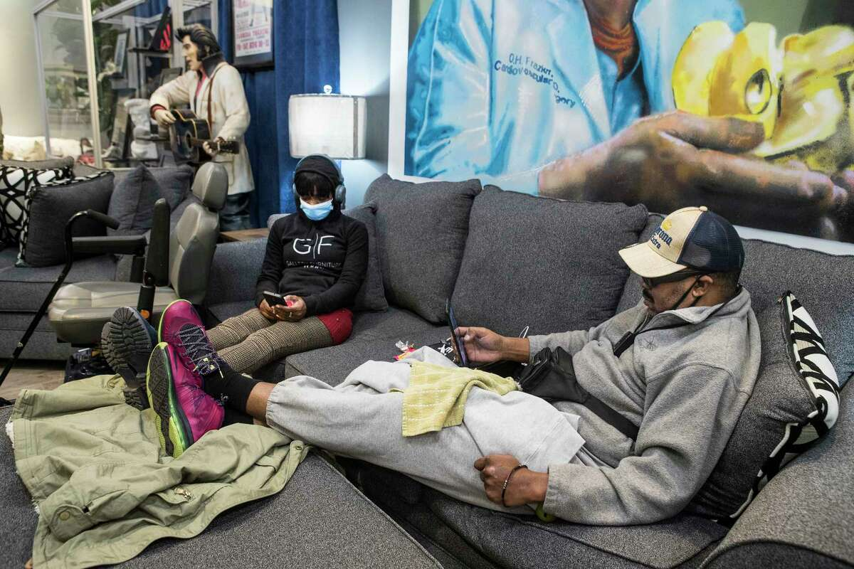 Iritha Stranton, left, and her husband Gregory Walters sit on a floor model couch at a warming shelter set up at Gallery Furniture Tuesday, Feb. 16, 2021 in Houston. As emperatures stayed below freezing Tuesday, and many in the neighborhood around the furniture store without power, Jim