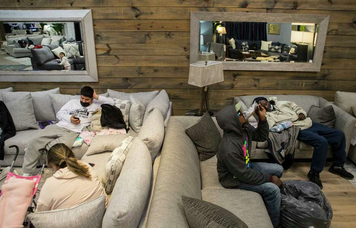 People gather at a warming shelter set up at Gallery Furniture Tuesday, Feb. 16, 2021 in Houston. As emperatures stayed below freezing Tuesday, and many in the neighborhood around the furniture store without power, Jim