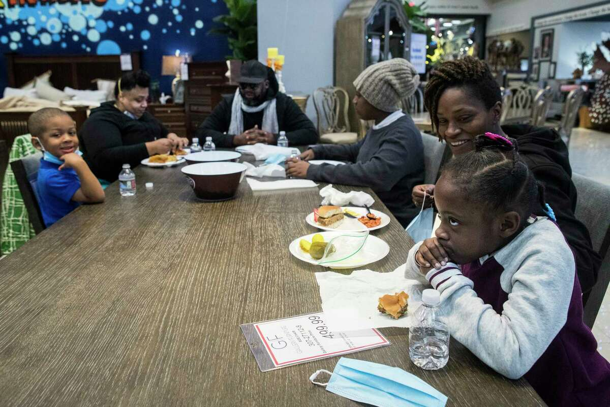 Joecyah Heath, from left, Joeanna Heath, Jermell Heath, Jenesis Heath and June Day and Morning Day, far right, share a meal together on a floor model dining room table at a warming shelter set up at Gallery Furniture Tuesday, Feb. 16, 2021 in Houston. As emperatures stayed below freezing Tuesday, and many in the neighborhood around the furniture store without power, Jim