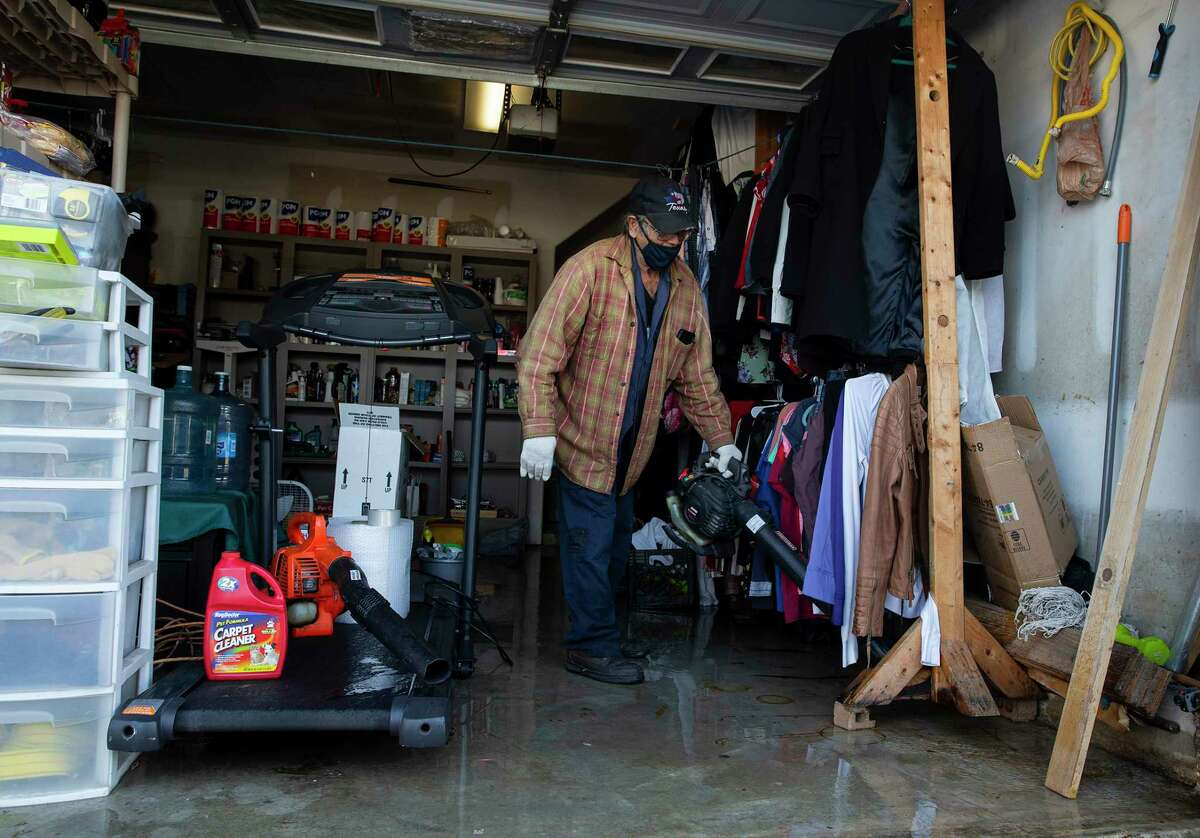 Joe A. helps to blow flood water out of his neighbor's garage Tuesday, Feb. 16, 2021, in South Houston. Sylvia Gomez lost power at her house and went to stay with her daughter in Pasadena last night, but came home to find her water pipes bursted and flooded her house.