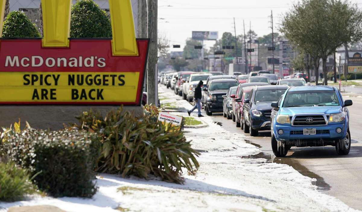 A long line of cars wait along FM 1960 to turn into McDonald's where the drive thru line continues around the restaurant Tuesday, Feb. 16, 2021 in Houston.