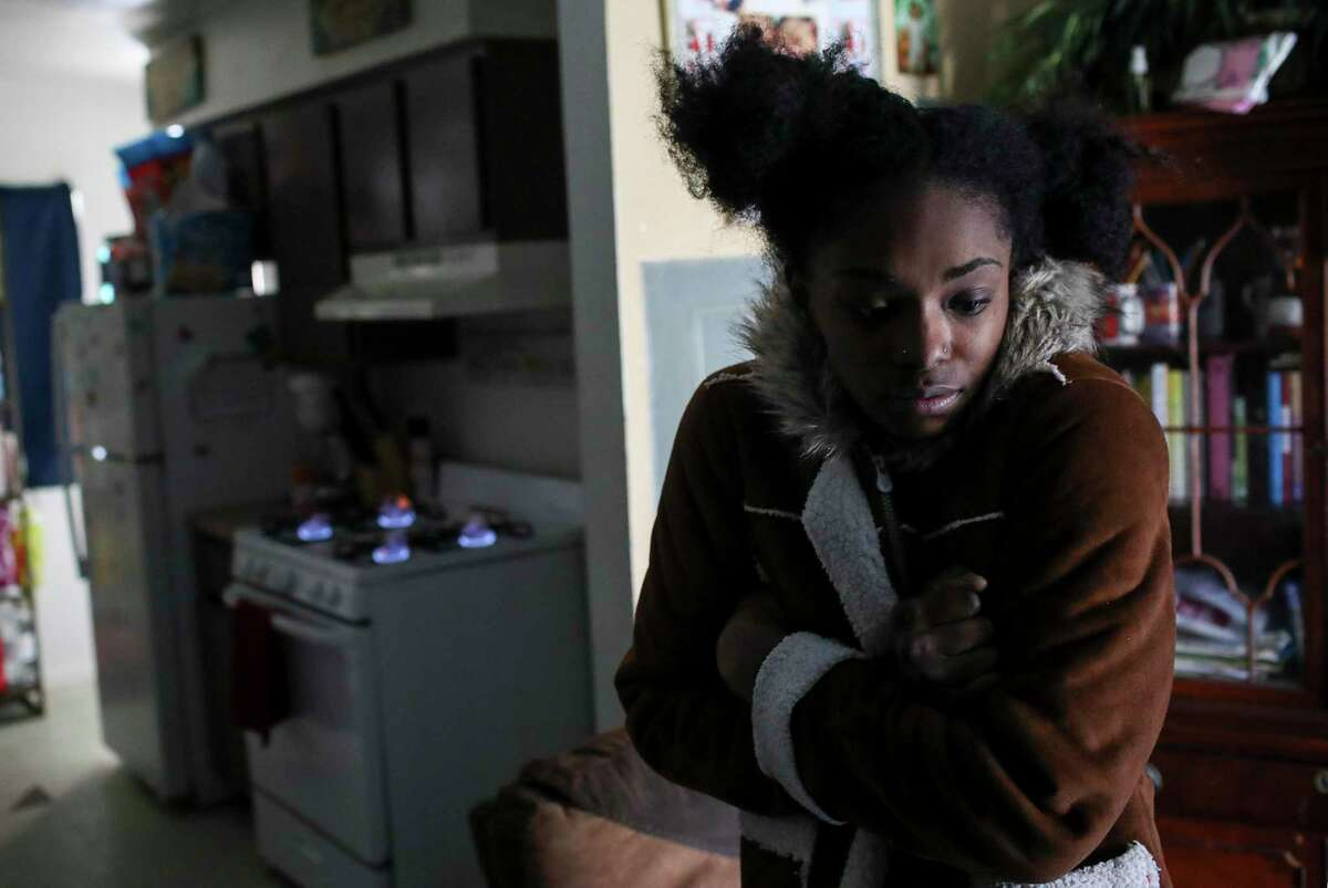 Shanice Ardion holds her jacket tight in her home as her stove burns in the background Tuesday, Feb. 16, 2021, at Cuney Homes in Houston. She said the stove was their only source of heat since their power has been out since yesterday.