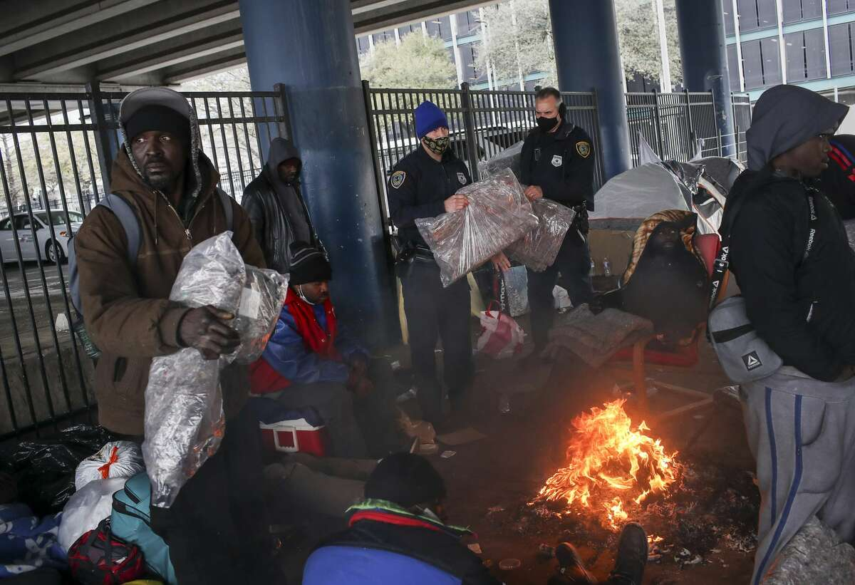 Houston Police officers Kenneth Bigger, center, and Aaron Day, center-right, hand out blankets to people as a winter storm continues to hit the area Tuesday, Feb. 16, 2021, under the elevated portion of I-45 in downtown Houston.