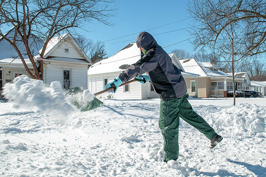 Deb Shade battles the cold Tuesday morning while shoveling snow from her driveway. Shade said she was happy at least to have blue skies and is looking forward to higher temperatures this weekend. Photo: Darren Iozia | Journal-Courier / Jacksonville Journal-Courier