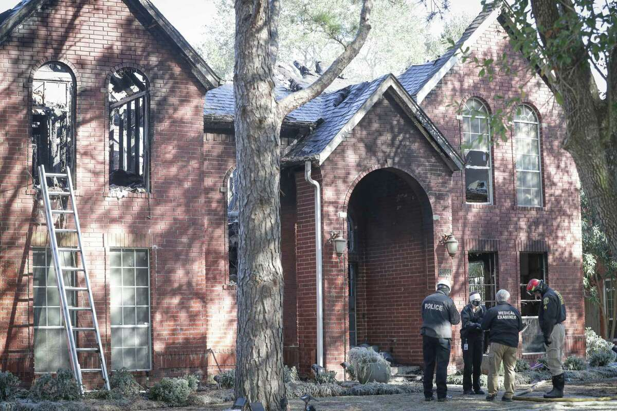 A medical examiner along with other investigators talk in front of a home where a grandmother and her three elementary-age grandchildren died Tuesday, Feb. 16, 2021, in Sugar Land.