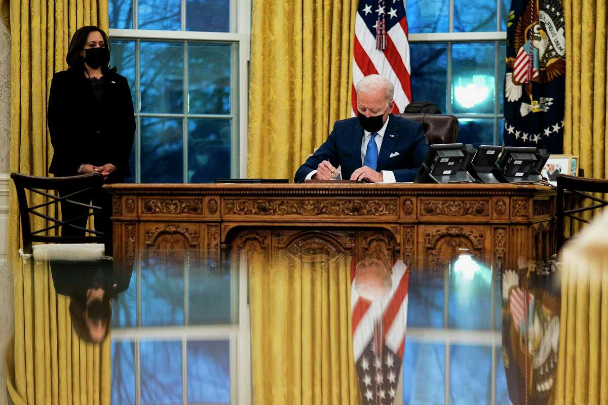 President Joe Biden signs several executive orders directing immigration actions for his administration as Vice President Kamala Harris looks on in the Oval Office at the White House in Washington, D.C., on Tuesday, Feb. 2, 2021. (Doug Mills/Pool/Getty Images/TNS)