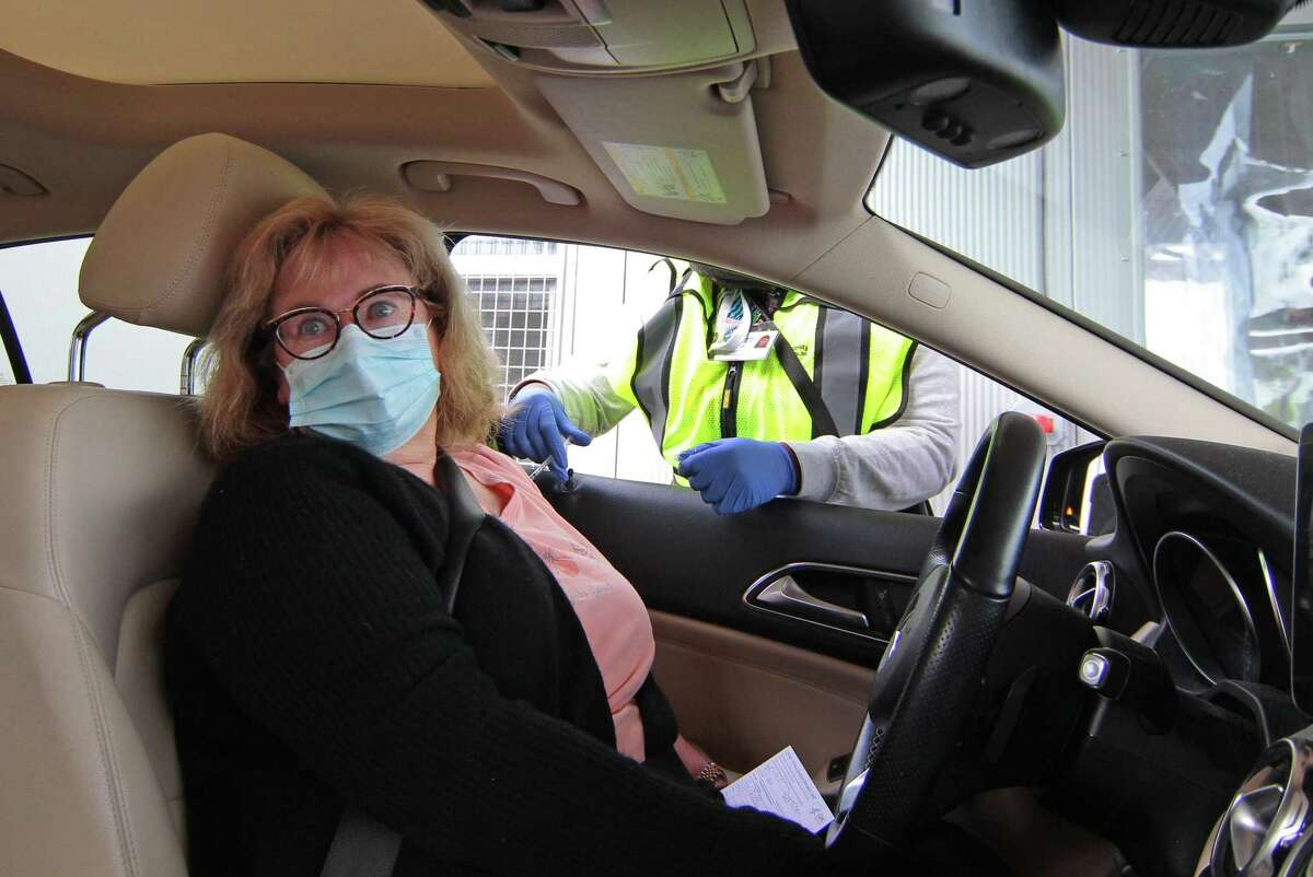 Gretchen Lupinacci, of Greenwich receives the Pfizer vaccine shot during Community Health Center's mass drive-through COVID-19 vaccination clinic held at the parking lot of Lord & Taylor in Stamford, Conn., on Wednesday Feb. 3, 2021.