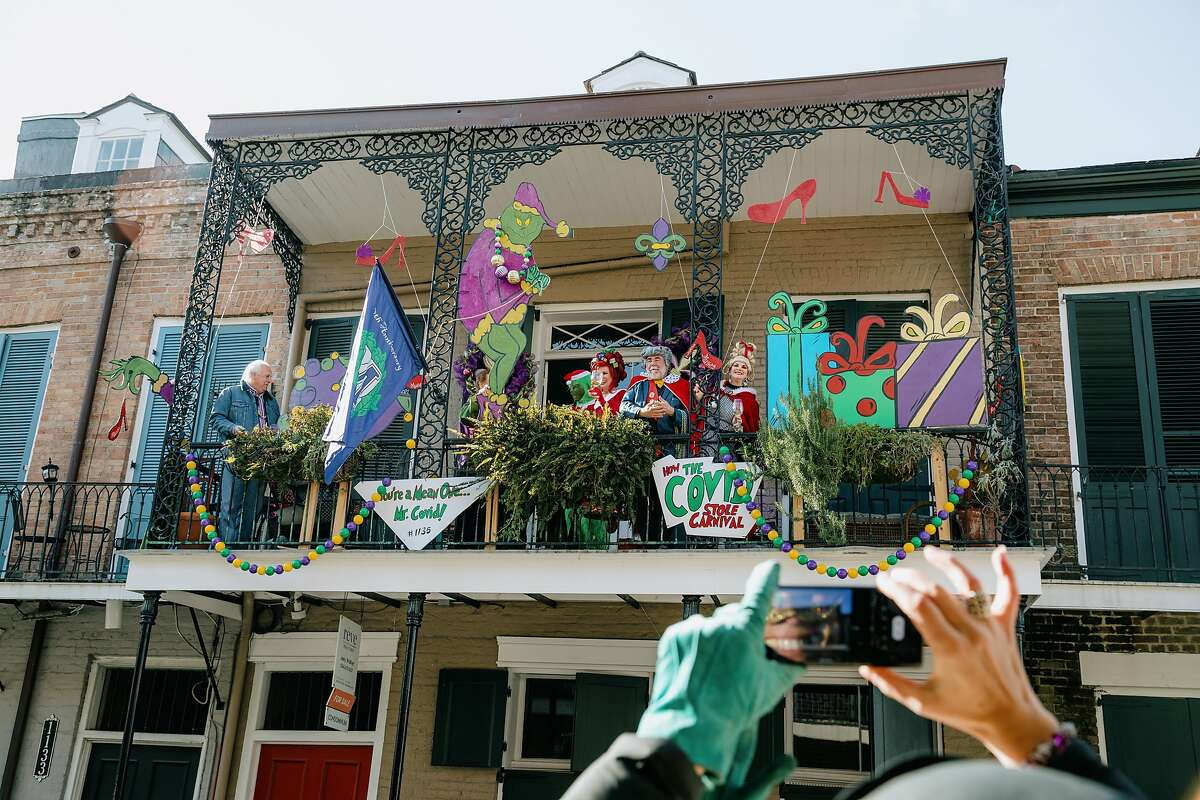 People dressed for Mardi Gras stand on a balcony near a sign that reads
