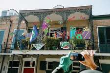 """People dressed for Mardi Gras stand on a balcony near a sign that reads """"How The Covid Stole Carnival"""" in the French Quarter neighborhood of New Orleans, Louisiana, U.S., on Tuesday, Feb. 16, 2021. Since 1857, Mardi Gras celebrations in New Orleans have been called off only 14 times, because of war, mob violence, or labor disputes. Not even the last great pandemic could quell the street parades. Mark the history books: This year will be the 15th. Photographer: Bryan Tarnowski/Bloomberg"""