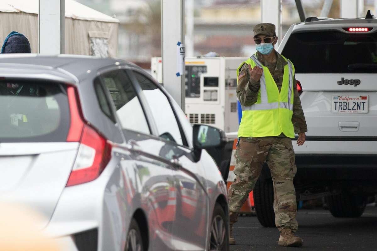 A California National Guard member directs a vehicle to receive their COVID-19 vaccine shot. A COVID-19 mass vaccination site opened to the public at the Oakland-Alameda Coliseum Complex in Oakland, Calif., on Feb. 16, 2021.