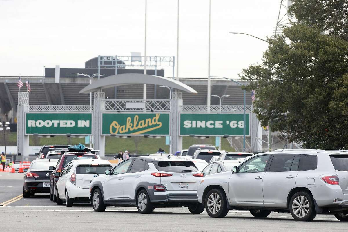 Vehicles line up to enter the COVID-19 mass vaccination site open to the public at the Oakland-Alameda Coliseum Complex in Oakland on Feb. 16, 2021.