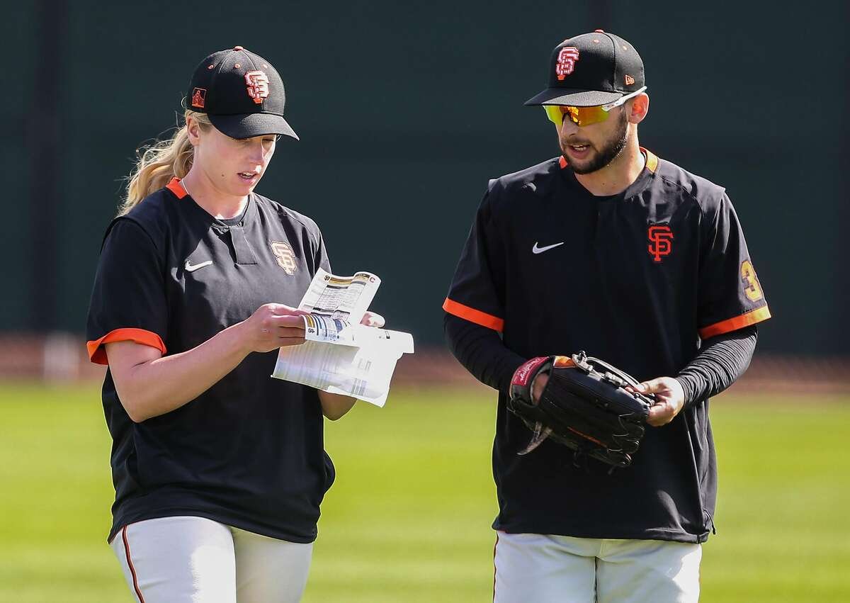San Francisco Giants' coach Alyssa Nakken talks with an outfielder during a practice at Scottsdale Stadium Thursday, March 5, 2020, in Scottsdale, Arizona.