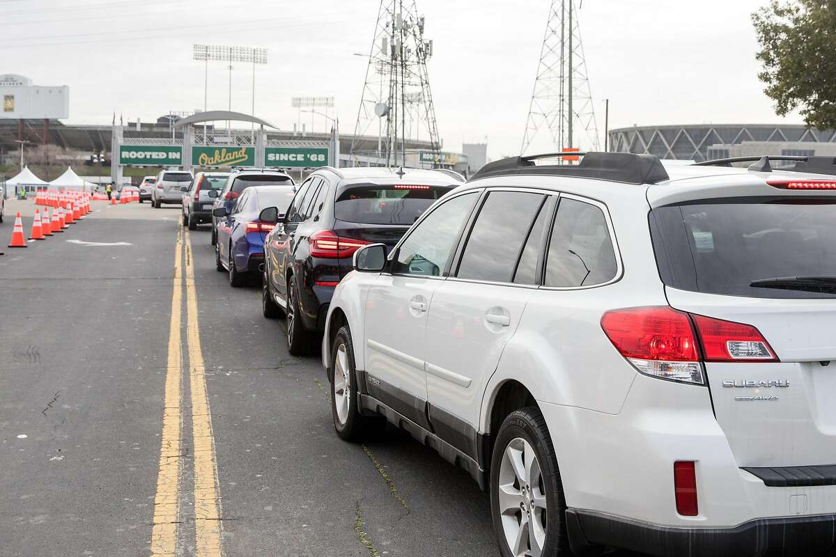 Vehicles line up to enter the COVID-19 mass vaccination site opened to the public at the Oakland-Alameda Coliseum Complex in Oakland, Calif., on Feb. 16, 2021. The site is expected to deliver up to 6,000 shots of COVID-19 vaccine a day.
