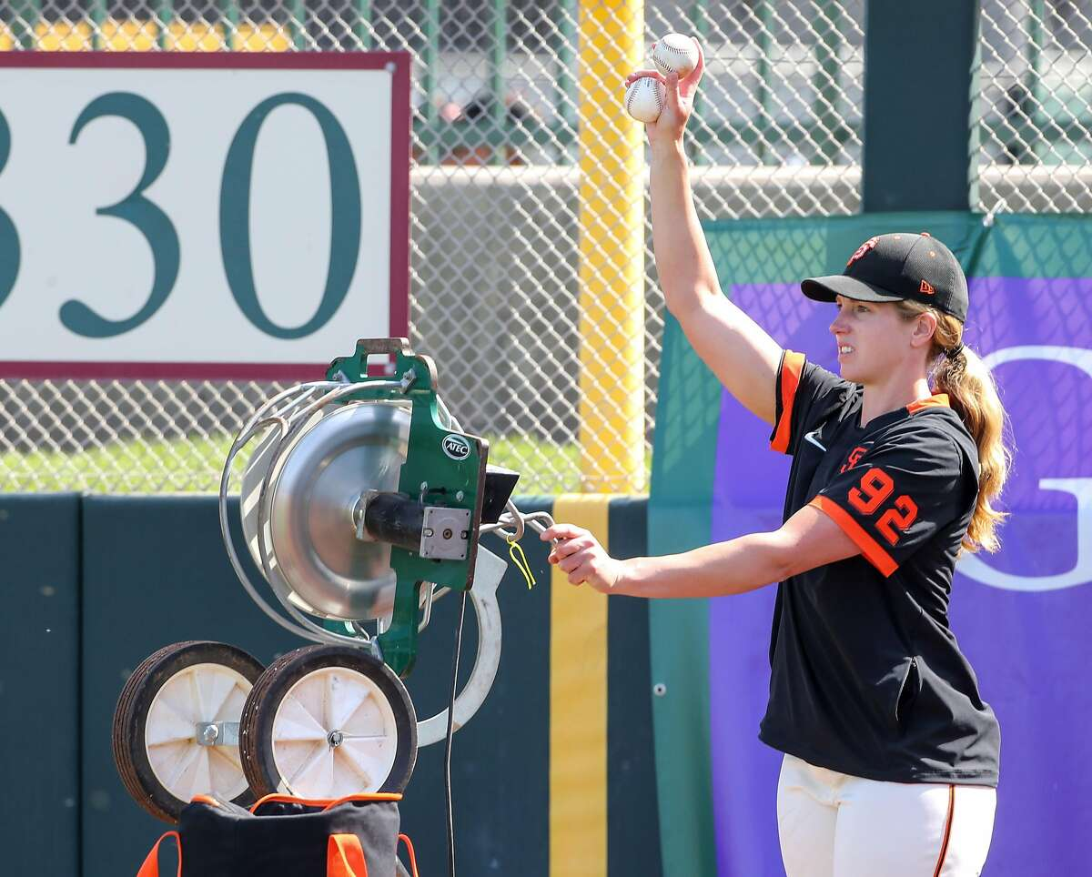 San Francisco Giants' coach Alyssa Nakken work with the outfielders before their game with the Cleveland Indians at Scottsdale Stadium Thursday, March 5, 2020, in Scottsdale, Arizona.