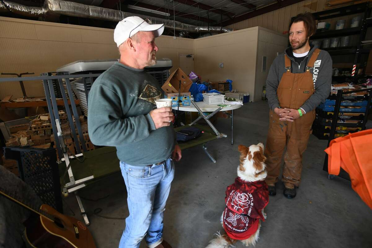 Wesley Coleman (left) talks with Michael Domingue, as Domingue's dog Bonnie sits nearby at Victory Temple in Beaumont, which opened to those in need of shelter from the storm Saturday and will remain open through Friday morning. Domingue made a wrong turn heading to Alabama from Louisiana when his truck broke down in Beaumont as the storm set in, annd he was told about the open shelter. Photo made Tuesday, February 16, 2021 Kim Brent/The Enterprise