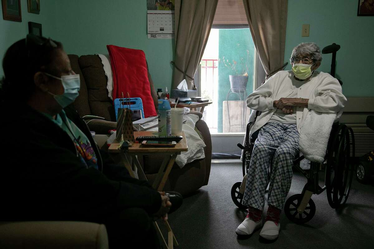 Maria Rodriguez, 79, talks with Herminia Rodriguez, 85, (no relation) in Herminia's apartment at the Ernest C. Olivares Senior Community Residence, where they both live, shortly after electricity returned to their apartments in San Antonio on Feb. 16, 2021. Around 5 p.m. they lost electricity again after several hours of having it on.