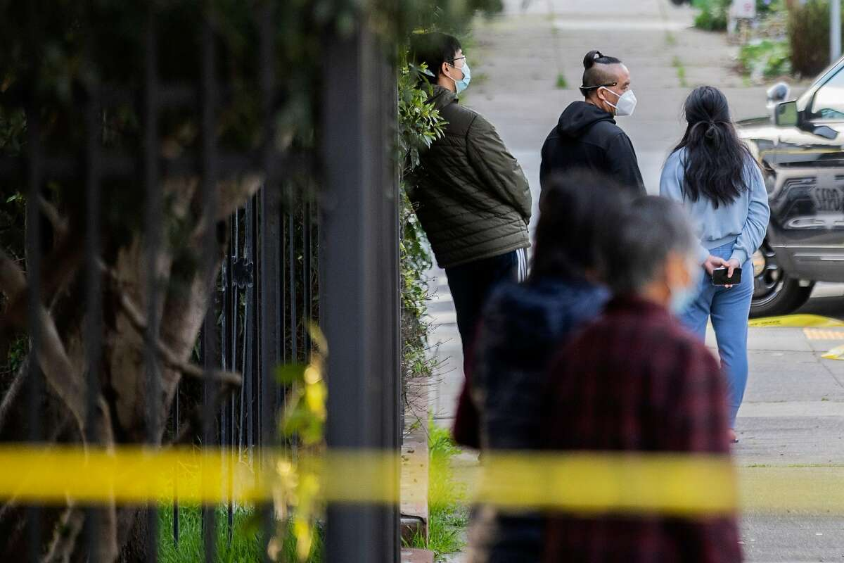 People in Visitacion Valley watch as San Francisco police search for a shooting suspect along Campbell Avenue near Delta Street, Tuesday, Feb. 16, 2021, in San Francisco, Calif. A shelter-in-place for people in the neighborhood was later lifted.