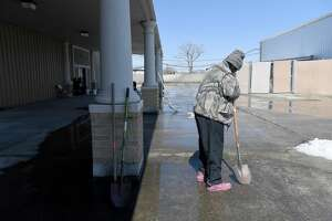 A shelter guest helps in clearing ice from outside the entry at Victory Temple in Beaumont, which opened to those in need of shelter from the storm Saturday and will remain open through Friday morning. Photo made Tuesday, February 16, 2021 Kim Brent/The Enterprise