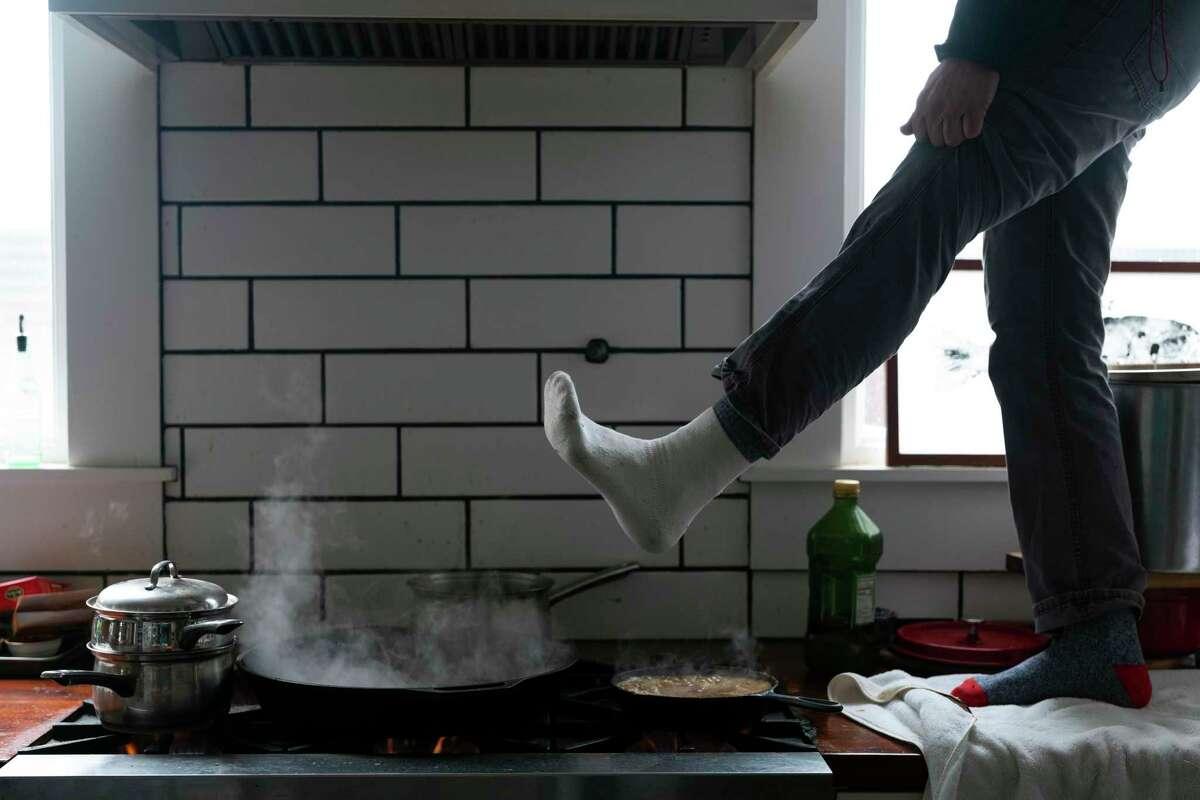Jorge Sanhueza-Lyon trata de calentar sus pies sobre una estufa de gas, el martes 16 de febrero de 2021, en Austin, Texas. (AP Foto/Ashley Landis)