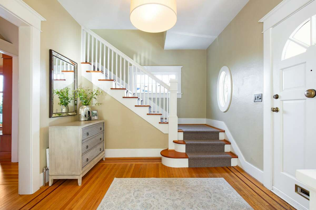 The home is multi-level, as we see from the entry with its glowing wood floor.