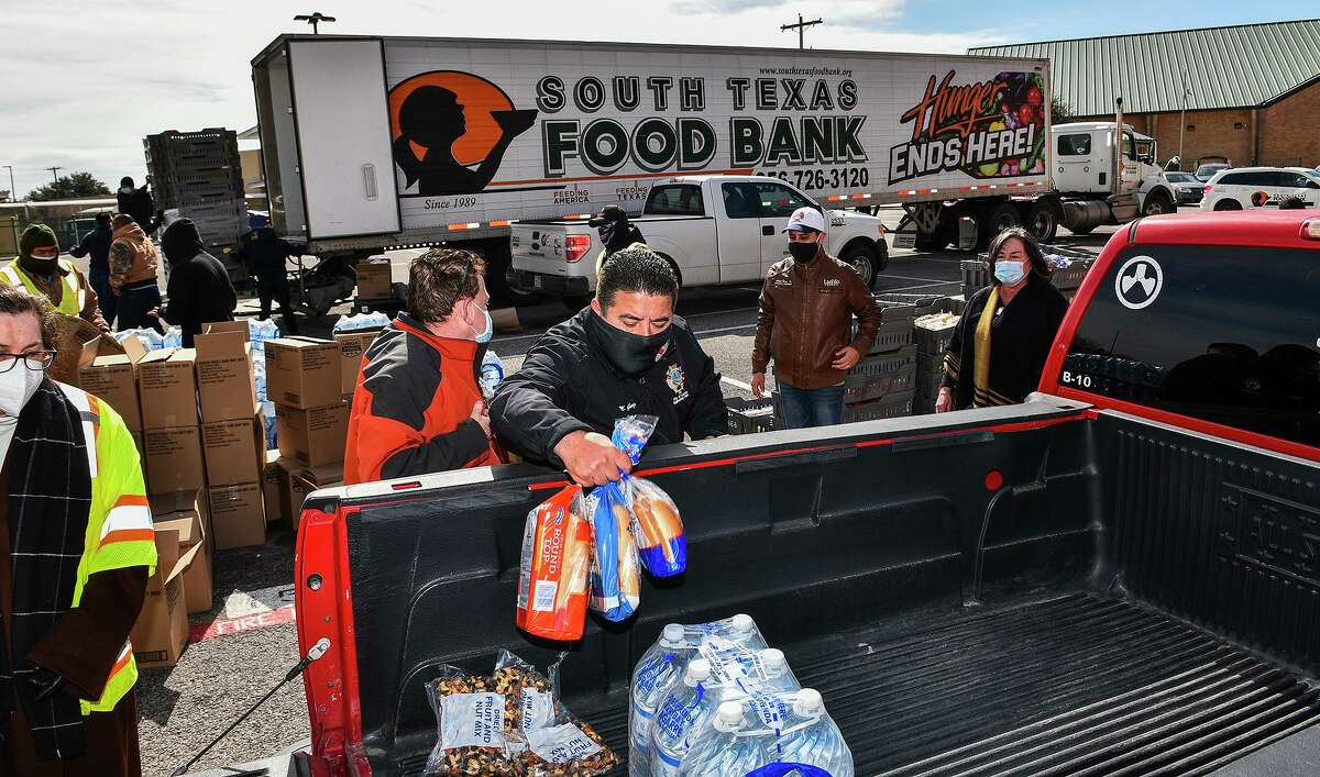 City workers and volunteers load supplies Tuesday to impacted locals from STFB at Nixon High School.