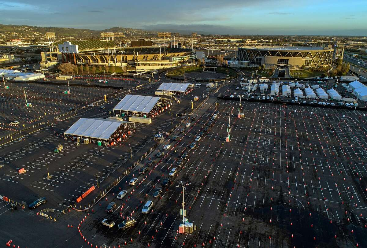 Drivers line up in their cars in the parking lot as vaccines were administered to the public for the first day of mass vaccinations at the Oakland Coliseum, February 16, 2021.