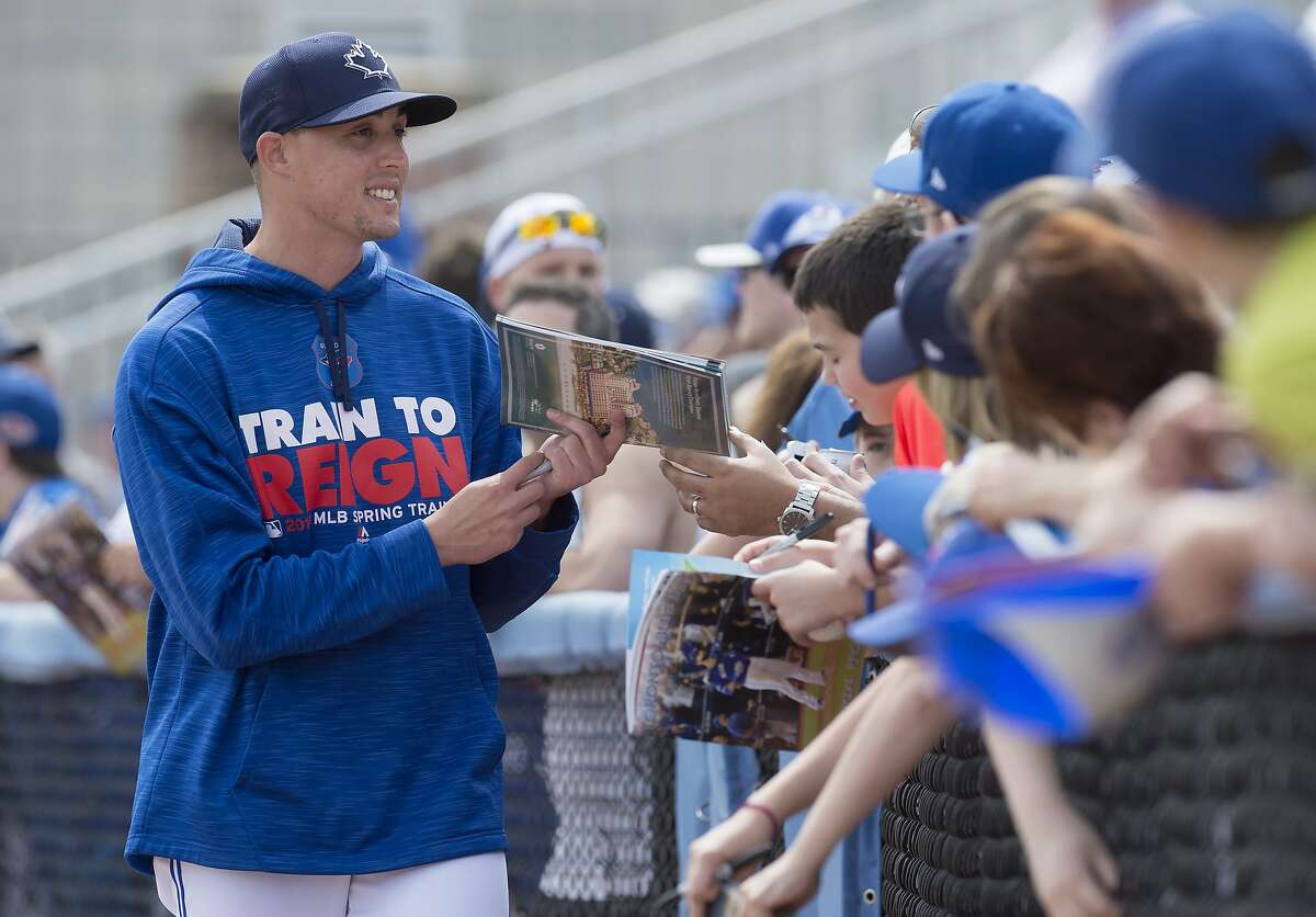Toronto Blue Jays pitcher Aaron Sanchez signs autographs for fans at an exhibition spring training baseball game against the Philadelphia Phillies in Dunedin, Fla., on Saturday, March 5, 2016. (Frank Gunn/The Canadian Press via AP) MANDATORY CREDIT