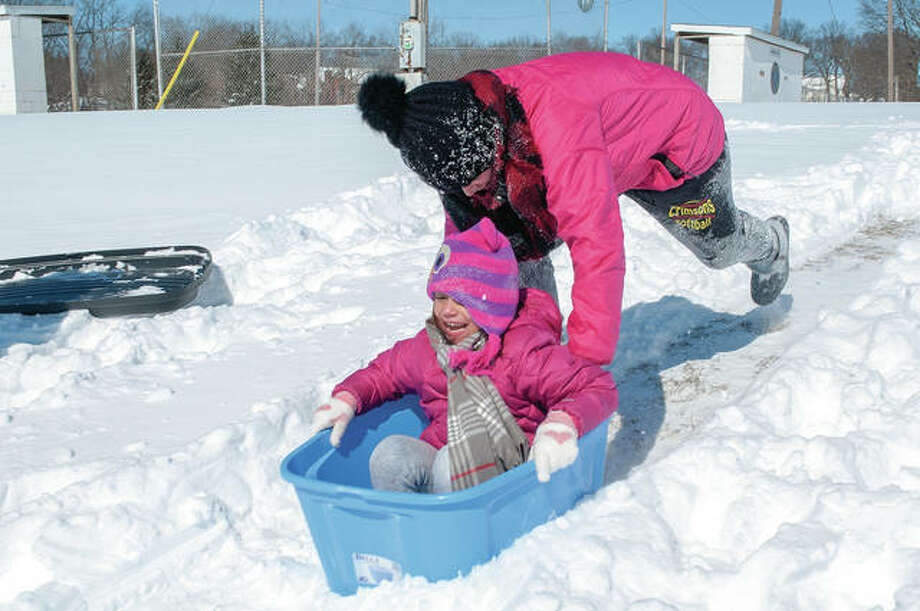Logann Padilla pushes her sister, Bailey, down a hill Tuesday outside Bob Freesen YMCA. Despite cold temperatures, the sisters were enjoying sledding. Photo: Darren Iozia | Journal-Courier