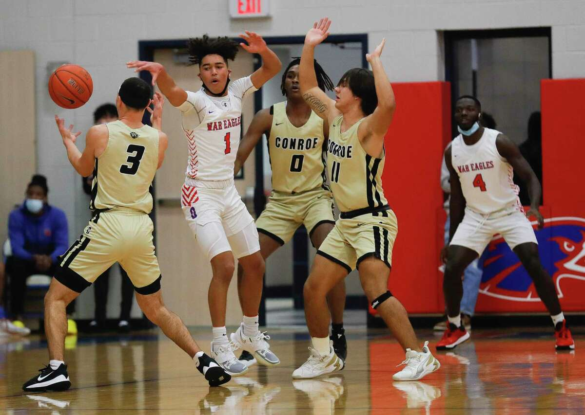 Conroe's Mikey Sneed (3) strips Oak Ridge's Ian Egele (1) of the ball as Ja'Len Moore (0) and Layne O'Dell (11) add pressure during the first quarter of a District 13-6A high school basketball game at Oak Ridge High School, Friday, Feb. 12, 2021.