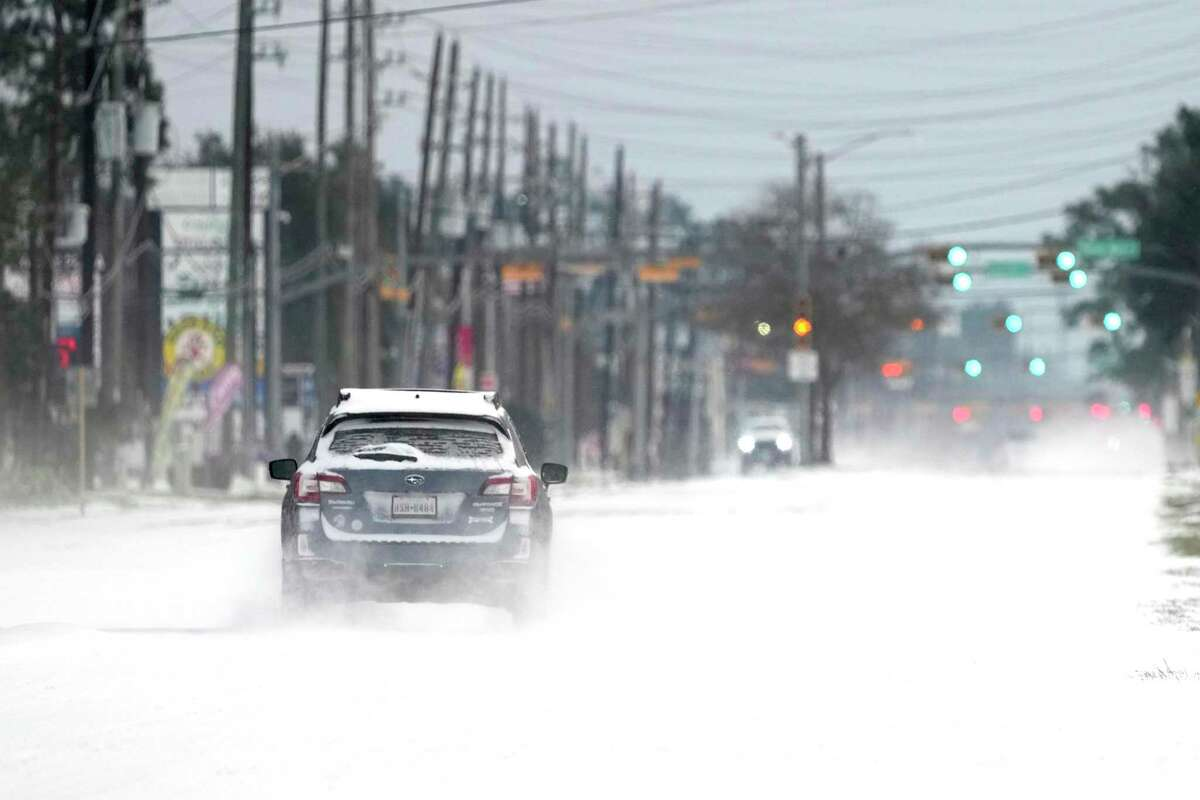 Vehicles drive on snow and sleet covered roads Monday, Feb. 15, 2021, in Spring, Texas. A winter storm dropping snow and ice sent temperatures plunging across the southern Plains, prompting a power emergency in Texas a day after conditions canceled flights and impacted traffic across large swaths of the U.S. (AP Photo/David J. Phillip)