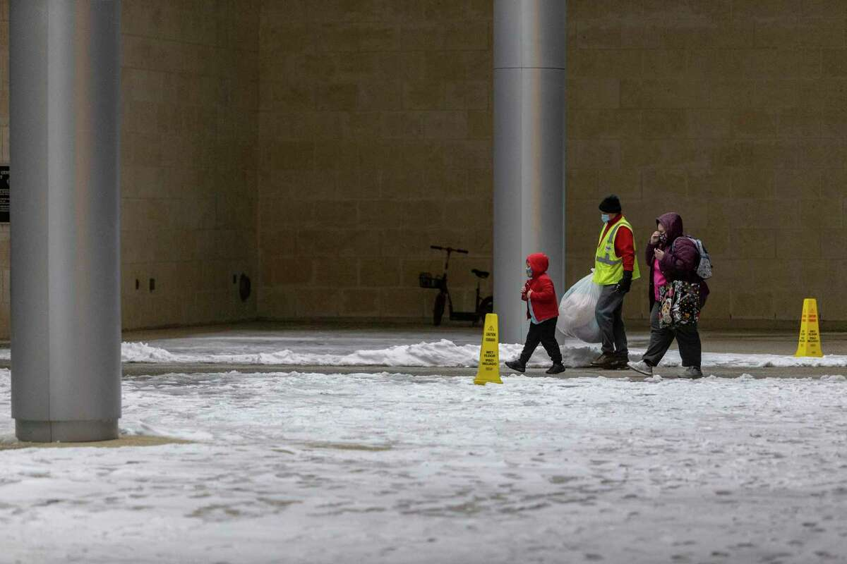 A woman and a child are helped Tuesday night to the Henry B. Gonzalez Convention Center where the city of San Antonio opened a warming center against the Arctic air mass that left hundreds of thousands without power.