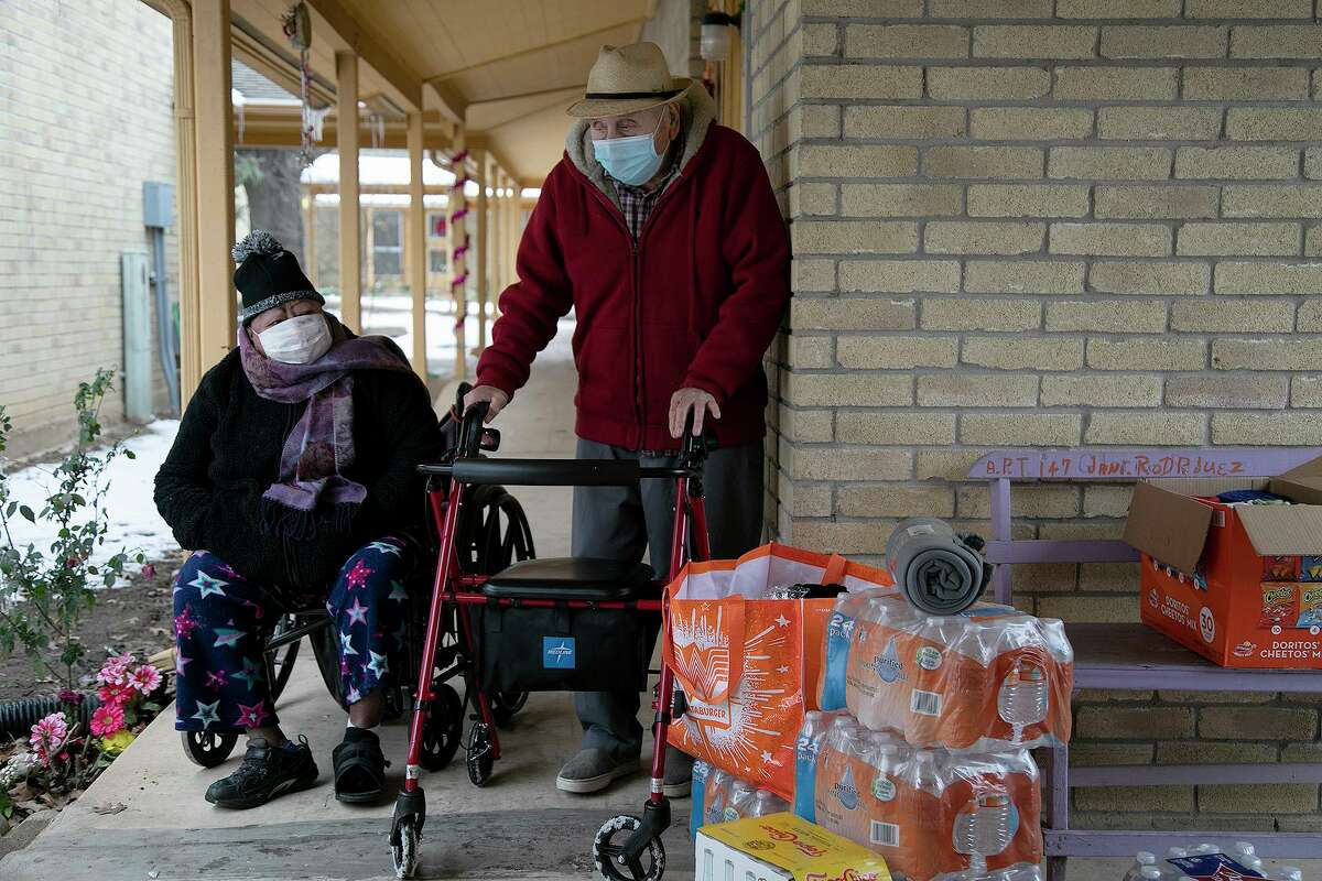 Janie Rodriguez, 69, left, and Isidoro Martinez, 86, stand outside where volunteers and community activists were delivering bags of food, blankets and socks provided by Eagles Flight Advocacy and Outreach to residents just minutes after electricity returned to their apartments at Col. George Cisneros Apartments on Tuesday in San Antonio. The residents were without electricity for several days.