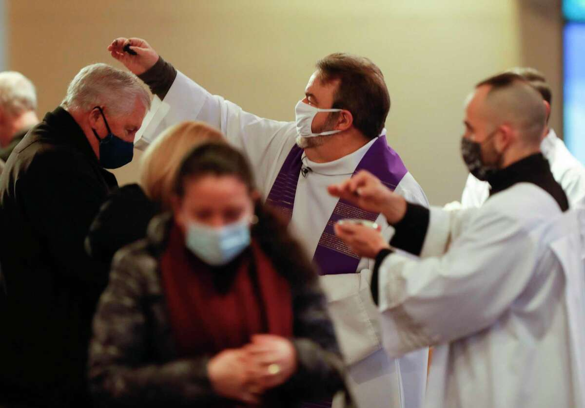 Father Tom Rafferty sprinkles ashes on a man's head as Catholics parishioners take part in an abbreviated Ash Wednesday service due to the weather at St. Anthony of Padua Catholic Church, Wednesday, Feb. 17, 2021, in The Woodlands.