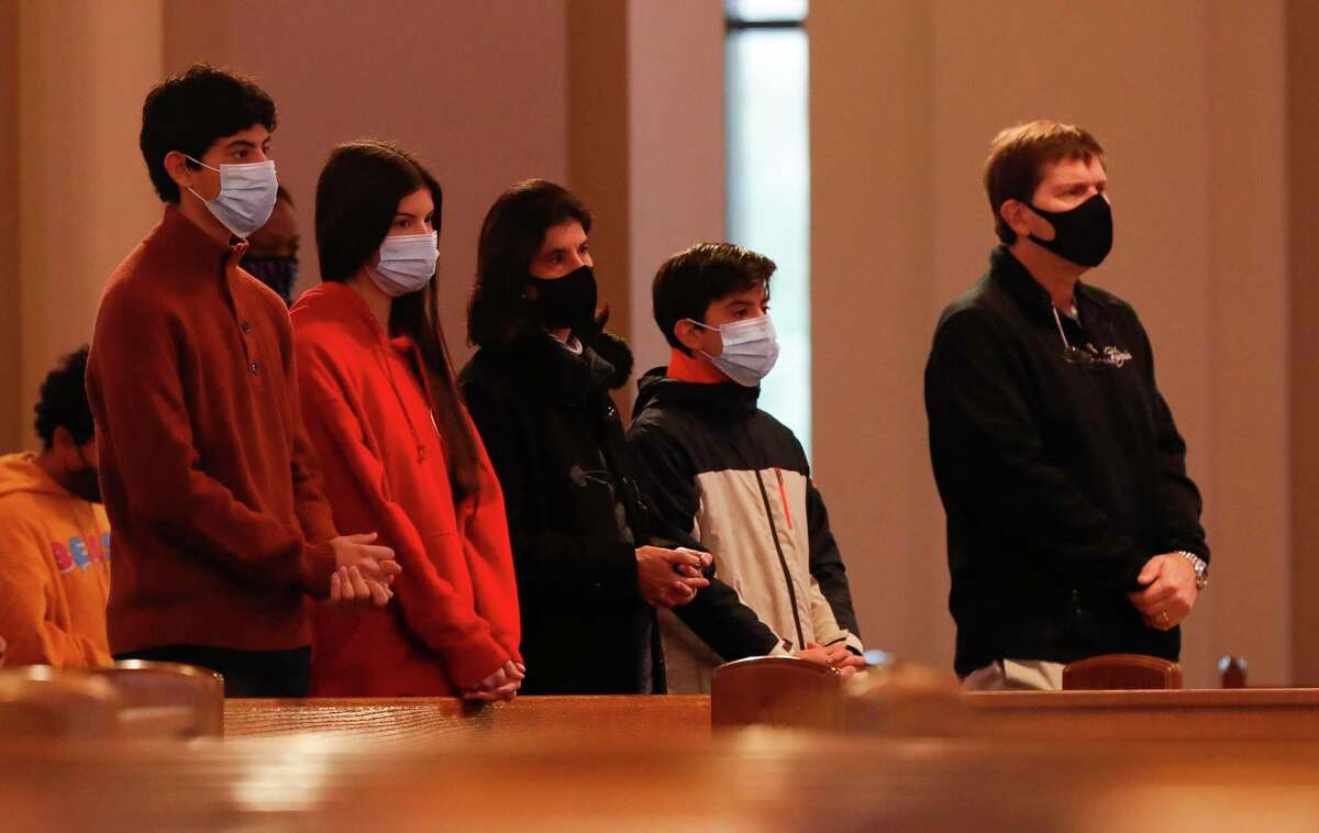 Catholics parishioners take part in an abbreviated Ash Wednesday service due to the weather at St. Anthony of Padua Catholic Church, Wednesday, Feb. 17, 2021, in The Woodlands.