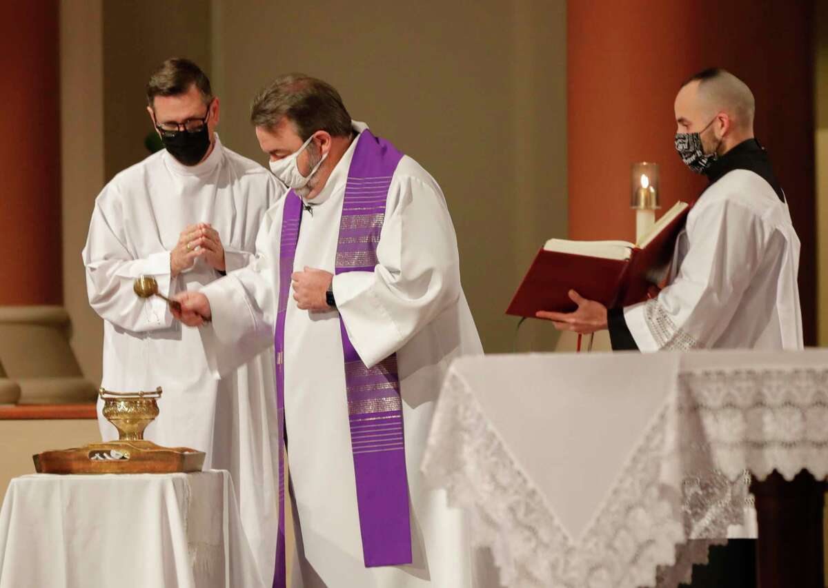 Father Tom Rafferty blesses ashes as Catholics parishioners take part in an abbreviated Ash Wednesday service due to the weather at St. Anthony of Padua Catholic Church, Wednesday, Feb. 17, 2021, in The Woodlands.